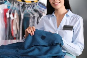 Female Worker With Stained Clothes At Dry-cleaner's, Closeup